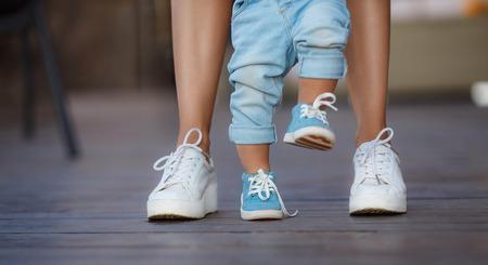 De eerste stappen van het kind, mamma in witte sneakers met een jonge zoon, gekleed in blauwe broek en blauwe schoenen, een warme zomerdag en leren lopen in de straat, de eerste stappen, de moeder houdt haar zoon.